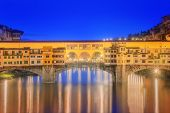 View of medieval stone bridge Ponte Vecchio and the Arno River from the Ponte Santa Trinita in Florence, Tuscany, Italy. poster