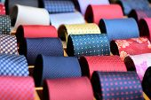 Photo of many different ties neckties cravats long pieces of cloth of various colors fabric material classic fashion accessory rolled on display for sale on blurred background horizontal picture poster