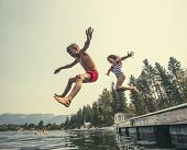 Kids jumping off the dock into a beautiful mountain lake. Having fun on a summer vacation at the lake with friends poster