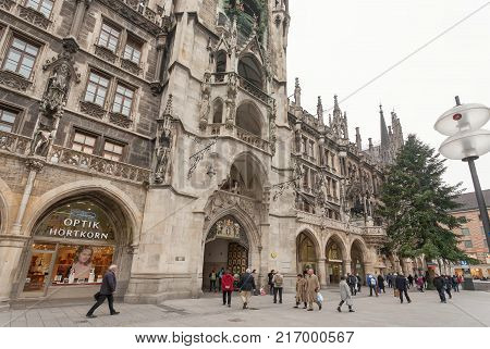 MUNICH, GERMANY - NOVEMBER 17, 2017: People walking past historical neo-Gothic style New Town Hall -Neues Rathaus- on November 17, 2017. Munich is the 12th largest city in the European Union