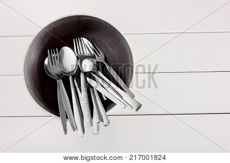 Forks and Spoons in Container on Wooden Background