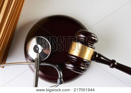 Law mallet or Judge gavel and medical stethoscope near law textbook in library archive study room, close-up. Forensic medicine investigation or malpractice justice concept