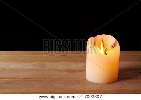 A Lighted Candle on a Wooden Background