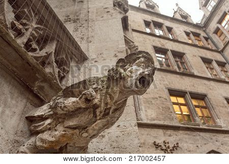 Screaming grotesque carved figure projecting from the gutter of a building. Stone gargoyle on building in Bavaria, Germany.