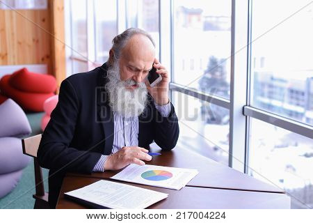 Retired old man give call to business partner with smart phone using new technology todeal with financial matters in summer in office. Handsome stately grey head man withlong beard in business suit sitting at table in studio in modern workspace. Concept o