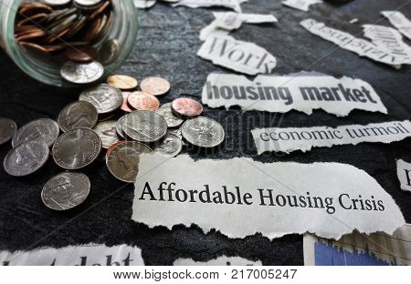 Affordable Housing Crisis newspaper headline and related economic news with coins