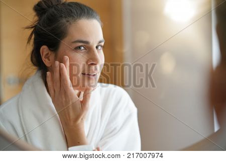 Woman in front of mirror applying cosmetics on
