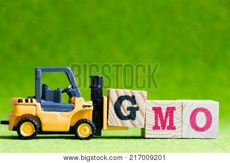 Toy forlift hold letter block G to fulfill word GMO (Abbreviation of Genetically Modified Organisms) on green background
