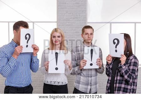 Group of people with signs on the sheets. The guy with the girl holding exclamation marks and on the sides people with closed faces sheets with a question mark