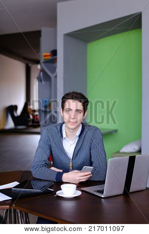 Portrait of self-assured male businessman who possing in camera and smilling, sitting at table with laptop and cup of tea in modern office in daytime. Man of European appearance with short dark curly hair dressed in white shirt and striped blue cardigan.