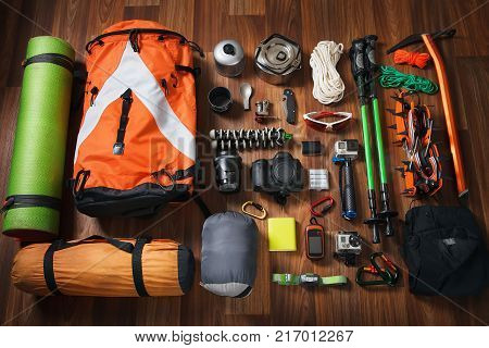 A variety of climbing equipment in large quantities on a wooden background from above. Sports travel extreme travel to the mountains outdoors. Backpack lokdorub sleeping bag flashlight camera for shooting photos and video. Wallpaper.