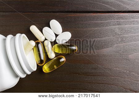 White and yellow capsules of glucosamine omega-3 pills of calcium on plastic box glass with water at wooden table top view.