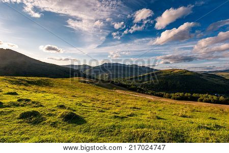 Grassy Rural Hillside At Cloudy Sunset