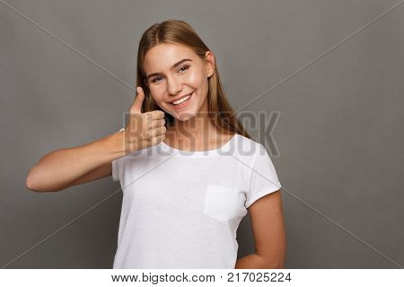 Happy young woman giving thumb up gesture. Smiling woman approve and recommend. Victory, luck, success concept