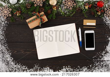 Preparing for holidays background. Wishlist, gift box, mobile, pen and credit card, garland frame, top view on wooden table with copy space. Seasonal sales, online sopping, Christmas presents concept