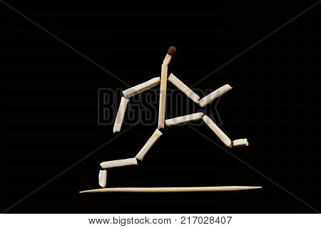 The running or jumping man. The figure of a man stilized by the matches on the black background. The objects are isolated and a clipping path is provided for easy extraction.