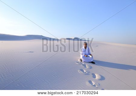 Beautiful Emirate Sheikh businessman studying project of future construction of complex, standing in middle of bottomless desert with white clean sand on clear warm day against blue sky. Swarthy Muslim with short dark hair dressed in kandura, long,