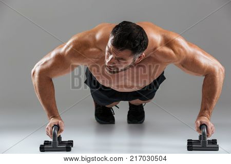 Close up portrait of a muscular strong shirtless male bodybuilder doing push-ups with bars isolated over gray background