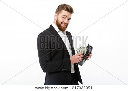 Happy bearded business man holding purse with money and looking at the camera over white background
