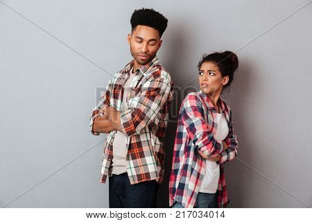 Portrait of an upset young african couple having an argument while standing back to back isolated over gray background