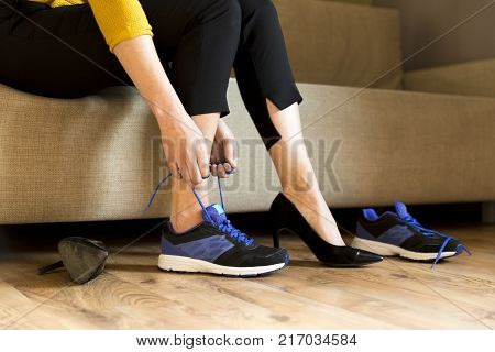 Woman changing high heels office shoes after working day while sitting on the couch ready to take a walk or run