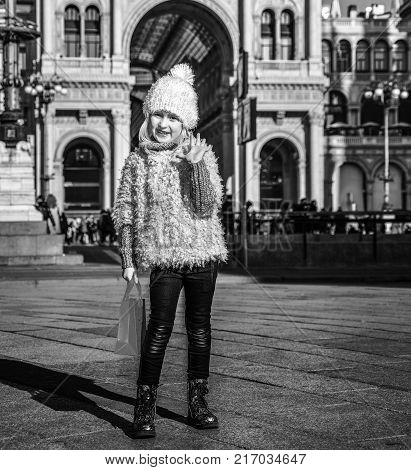 Rediscovering things everybody love in Milan. Full length portrait of happy elegant girl with red shopping bag in Milan Italy having fun time