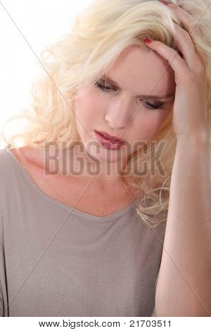 Blonde woman with her head in her hands