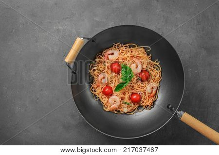 Wok with tasty pasta and shrimps on table, top view