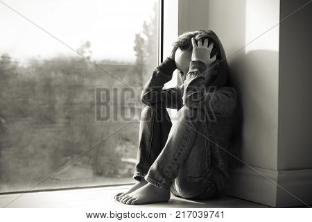 Little sad girl near window. Abuse of children concept