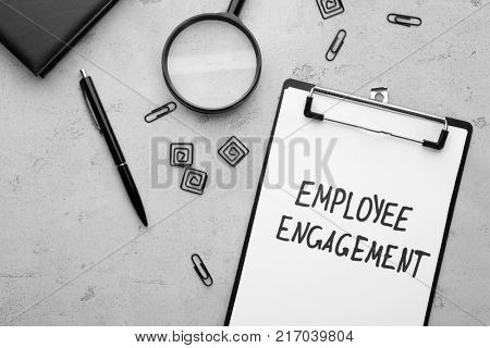 Clipboard with text EMPLOYEE ENGAGEMENT on table
