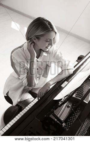 Talented woman playing piano indoors, black and white effect