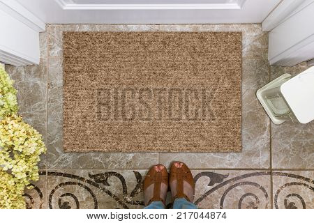 Blank doormat before the door in the hall. Mat on ceramic floor, flowers and shoes. Welcome home, product Mockup.