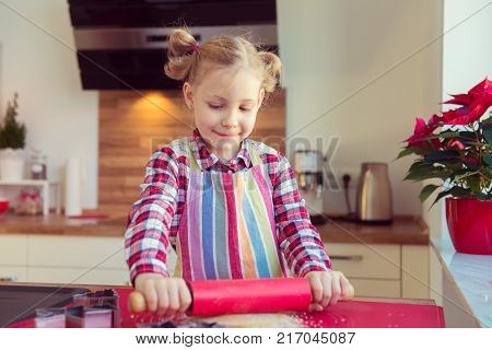 Pretty Little Girl With Funny Pigtails Making Christmas Cookies In Modern Kitchen