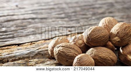 Dried nutmegs set on an old wooden surface. Space for text. Close up view.
