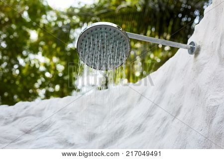 Outdoor rain shower head under palm trees and sunny beautiful blue sky. Living and nature harmony, spa resort hotel lifestyle.