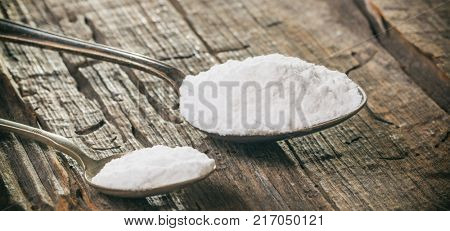 Tablespoon and teaspoon with baking soda, on wooden surface. Close up view.