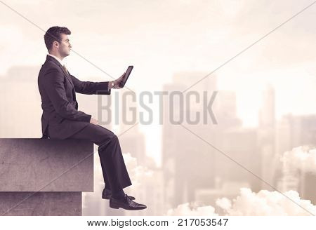 A serious business person sitting with laptop and tablet at the edge of a tall building, looking over cloudy city scape concept