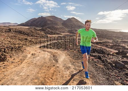 Trail runner male athlete running in nature rocky volcanic mountain background. Active fit sports man in compression sportswear sprinting on rocks path working out cardio training body.