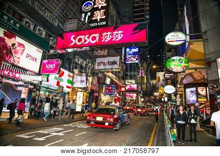 HONG KONG, CHINA- APR 2, 2016: Shopping street with illuminated advertisings and unidentified people at night on Apr 2, 2016. Hong Kong ranks as the worlds 4th most densely populated sovereign state
