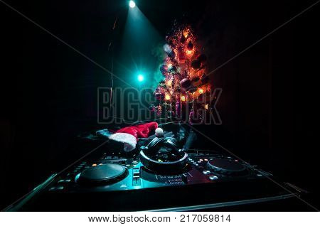 Dj Mixer With Headphones On Dark Nightclub Background With Christmas Tree New Year Eve. Close Up Vie