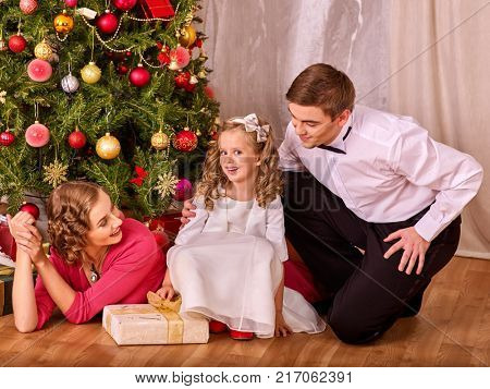 Family with child dressing Christmas tree. Xmas tree presents scene for happy family. Holiday family home portrait. Fun party.