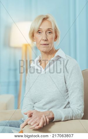 Looking serious. Calm thoughtful aged woman looking serious while being home alone and sitting on a comfortable sofa