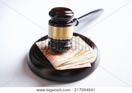 Law gavel, judge mallet or auctioneer's hammer and money stack isolated on white background with copy space, Corruption and financial crime theme. Concept of auction, close-up