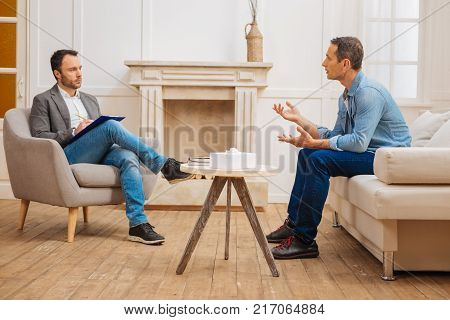 Time to relieve. Handsome man sitting on the couch while gesturing and taking in front of psychologist