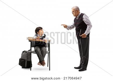 Teacher scolding a little schoolboy seated in a school chair isolated on white background