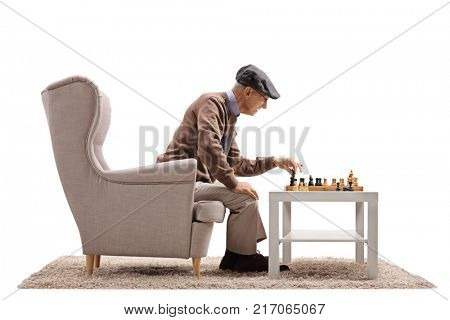 Elderly man sitting in an armchair and playing chess with himself isolated on white background