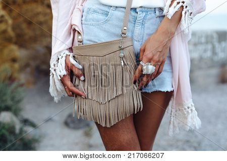 Young beautiful pretty stylish girl wearing jeans shorts and jacket, outdoors