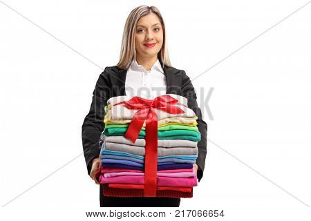 Formally dressed woman holding a stack of clothes wrapped with red ribbon as a gift isolated on white background