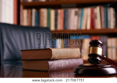 Judge's Gavel or mallet on wooden table with law books background. Courtroom theme close-up. Education and legal law concept
