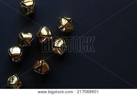 Black background with gold jingle bells. Copy space.